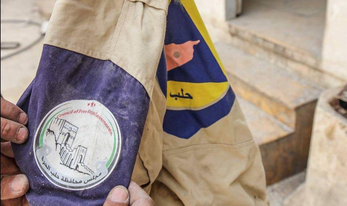 Al Nusra Front, Al Qaida i Syria logo på White Helmets uniform.